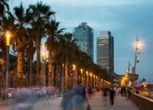 Illuminated quay next to Barceloneta beach in Barcelona with blurred people